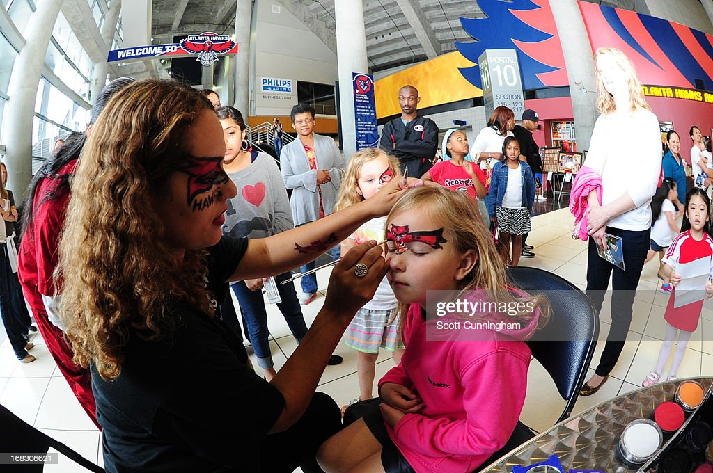 A young fan gets her face painted with the Atlanta Hawks logo before the game against the Indiana Pacers in Game Three of the Eastern Conference Quarterfinals in the 2013 NBA Playoffs on April 27, 2013 at Philips Arena in Atlanta, Georgia.