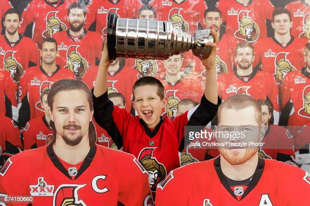 A young fan hams it up with a mini Stanley Cup model prior to the start of the game between of the Ottawa Senators and the New York Rangers in Game...