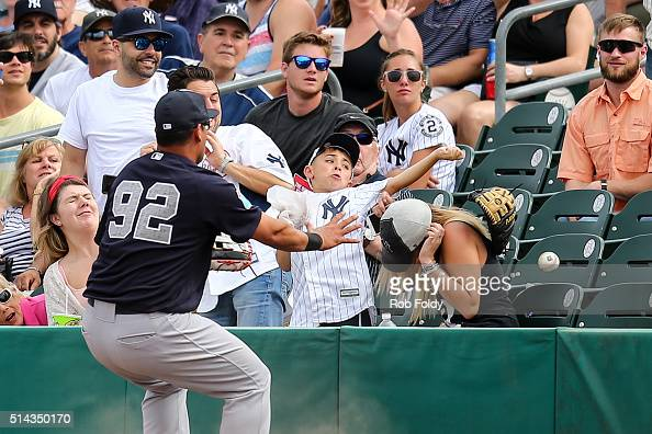 A young fan has his glove knocked off attempting to catch a foul ball as Sebastian Valle of the New York Yankees looks on during the spring training...