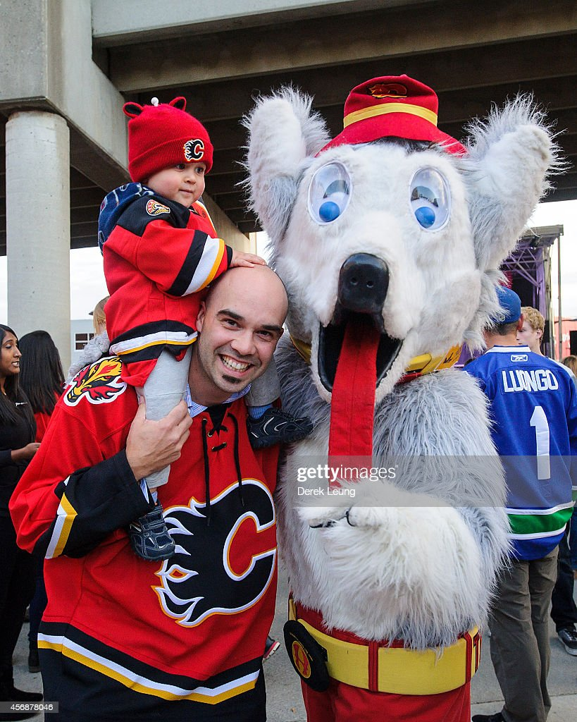A young fan his father and Harvey the Hound pose for a photograph prior to an NHL game between the Calgary Flames and the Vancouver Canucks at...