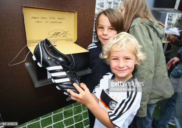 A young fan holds a football shoes at the adidas stand during the training session and the German fan party at the TUI Arena on October 7 2008 in...