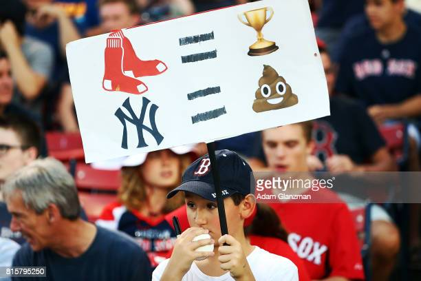 A young fan holds a sign with emojis during game two of a doubleheader between the Boston Red Sox and the New York Yankees at Fenway Park on July