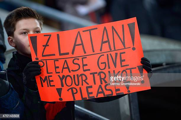 A young fan holds up a sign to Zlatan Ibrahimovic of PSG during the UEFA Champions League Round of 16 first leg match between Bayer Leverkusen and...