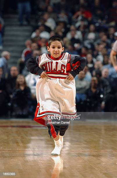 A young fan in an oversized Chicago Bulls uniform runs across the basketball court during an intermission in the game against the Orlando Magic at...