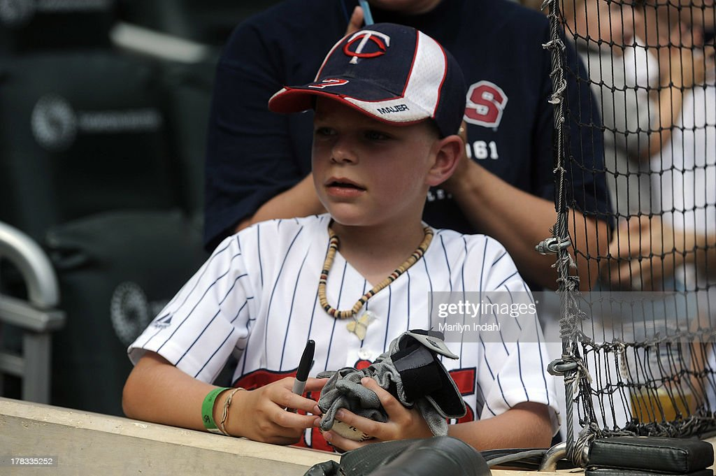 A young fan is given gloves by Josh Willingham #16 of the Minnesota Twins prior to the game against the Kansas City Royals at Target Field on August 29, 2013 in Minneapolis, Minnesota.
