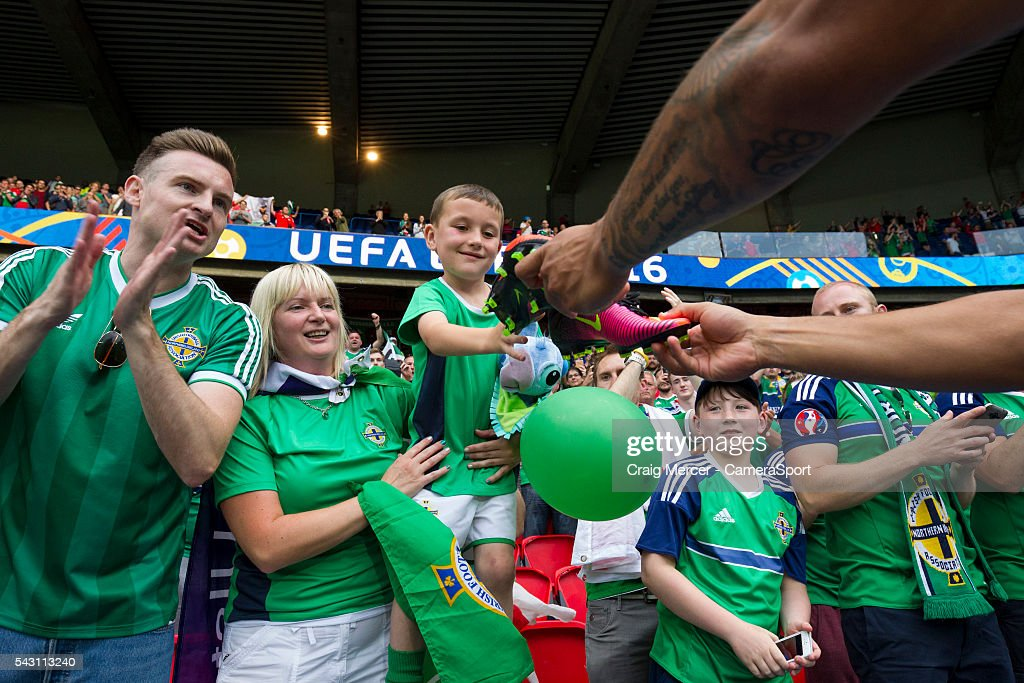 A young fan is given the boots of Northern Ireland's Josh Magennis during the UEFA Euro 2016 Round of 16 match between Wales and Northern Ireland at Parc des Princes on June 25 in Paris, France.