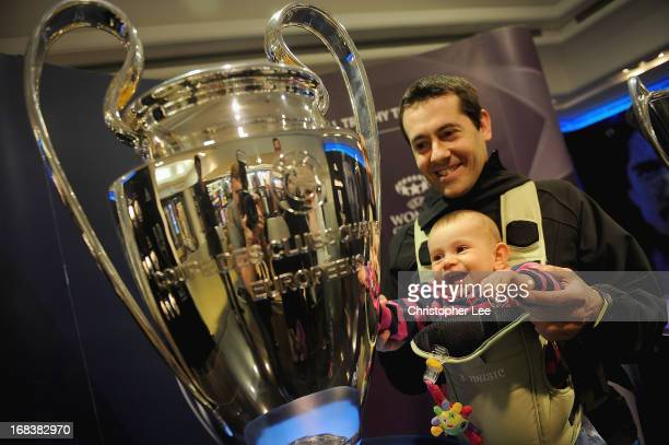A young fan is shown the Champions League trophy by her father during the Champions League Trophy Tour at Harrods on May 9 2013 in London England