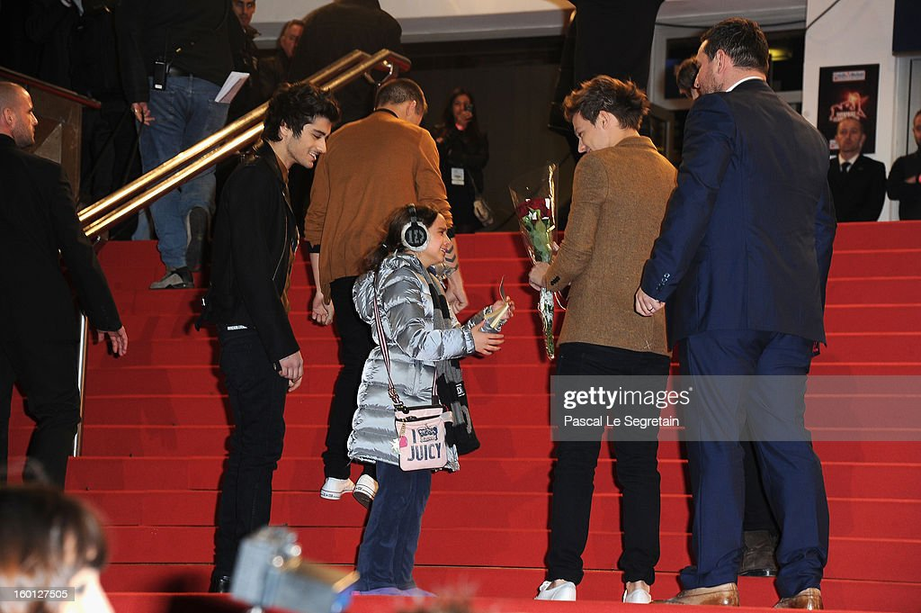 A young fan meets Louis Tomlinson of band 'One Direction' (R) during the NRJ Music Awards 2013 at Palais des Festivals on January 26, 2013 in Cannes, France.