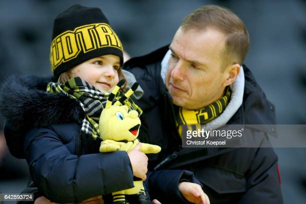 A young fan of Dortmund and her father are seen prior to the Bundesliga match between Borussia Dortmund and VfL Wolfsburg at Signal Iduna Park on...