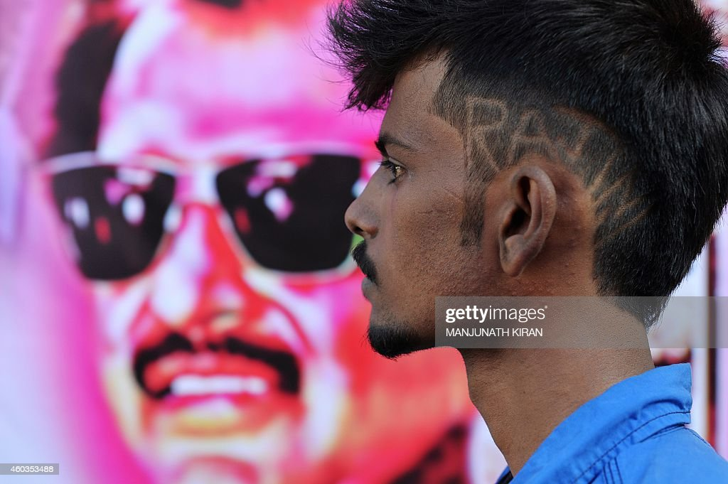 A young fan of Indian film actor Rajinikant, sporting the star's name in his hair-do, arrives at a movie theatre in Bangalore on December 12, 2014 on the occasion of the release of his movie 'Linga' which coincides with Rajinikant's 64th birthday. The movie is being simultaneously released on 5000 screens worldwide and was made with a budget of 125 crore rupees (200 million US dollars). AFP PHOTO/Manjunath KIRAN