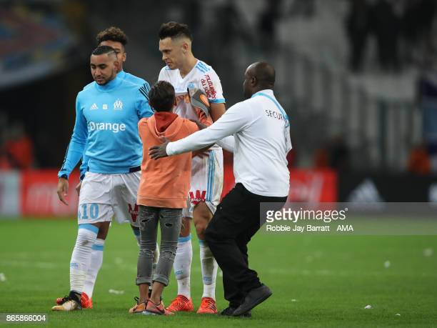 A young fan of Marseille runs on to the pitch at full time to meet Lucas Ocampos of Marseille during the Ligue 1 match between Olympique Marseille...
