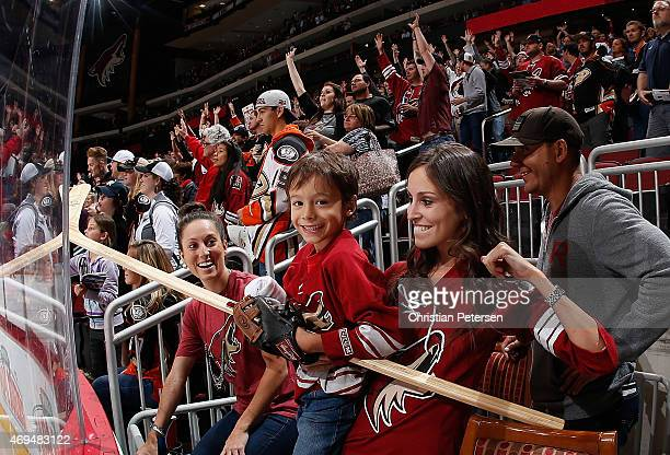 A young fan of the Arizona Coyotes smiles after being giving a stick for fan appreciation following the NHL game against the Anaheim Ducks at Gila...