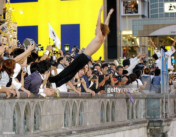 A young fan of the Hanshin Tigers dives into the Osaka river to celebrate the team's first league championship win in 18 years 15 September 2003...