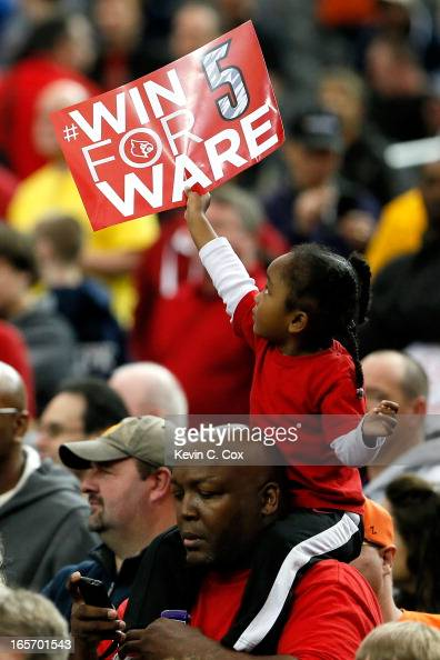 A young fan of the Louisville Cardinals holds up a sign which reads 'Win for Ware' in reference to injured Louisville guard Kevin Ware who suffered a...