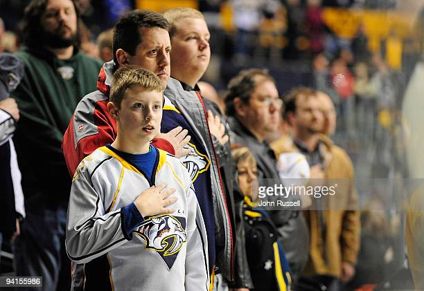 A young fan of the Nashville Predators holds his hand over his heart during the National Anthem prior to a game against the Vancouver Canucks on...
