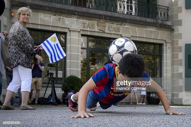 A young fan of Uruguayan forward Luis Suarez plays with his ball in front of the Court of Arbitration for Sport on August 8 2014 in Lausanne Suarez...