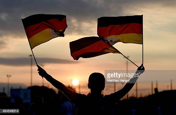 A young fan outside the stadium waves with flags prior to the international friendly match between Germany and Argentina at EspritArena on September...