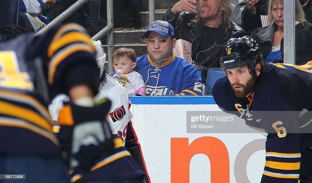 A young fan pays close attention as Mike Weber #6 of the Buffalo Sabres lines up for a faceoff against the Ottawa Senators on April 5, 2013 at the First Niagara Center in Buffalo, New York.