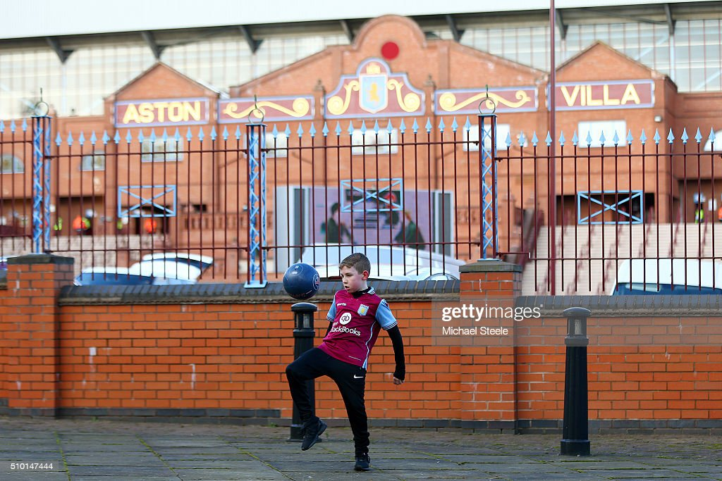 A young fan plays football outoside the stadium before the Barclays Premier League match between Aston Villa and Liverpool at Villa Park on February 14, 2016 in Birmingham, England.