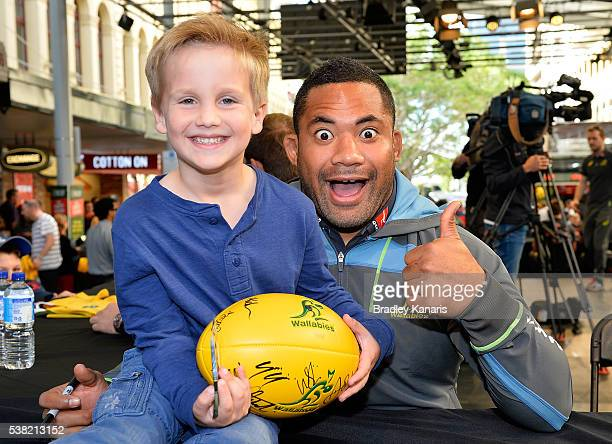 A young fan poses for a photo with Tatafu PolotaNau during an Australian Wallabies Fan Day at Queen Street Mall on June 5 2016 in Brisbane Australia