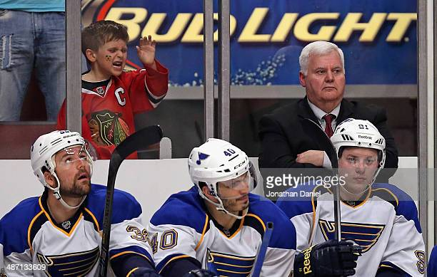 A young fan pounds on the glass as head coach Ken Hitchcock of the St Louis Blues watches the finals minutes along with team members on the bench...