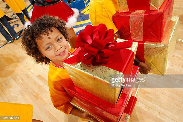 A young fan receives Christmas gifts from the Golden State Warriors during the NBA season opener against the Los Angeles Clippers on December 25 2011...