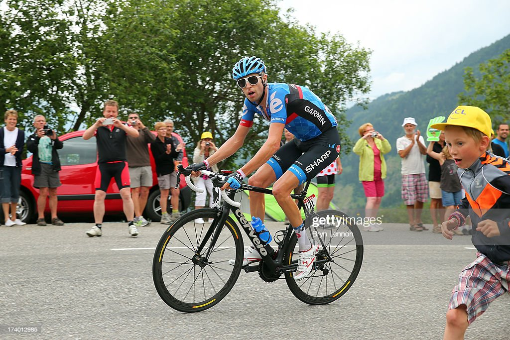 A young fan runs alongside Ryder Hesjedal of Canada and Team Garmin-Sharp during stage nineteen of the 2013 Tour de France, a 204.5KM road stage from Bourg d'Oisans to Le Grand Bornand, on July 19, 2013 in Le Grand Bornand, France.