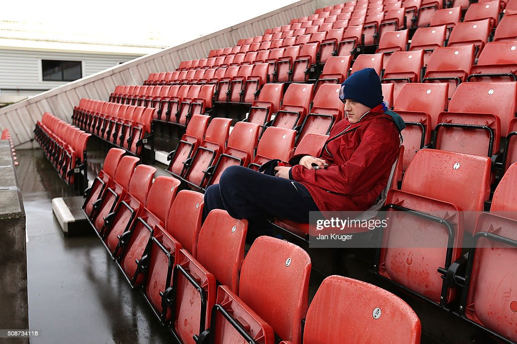 A young fan shields from the rain in the stands during the Barclays Premier League match between Stoke City and Everton at Brittania Stadium on February 06, 2015 in Stoke on Trent, England.