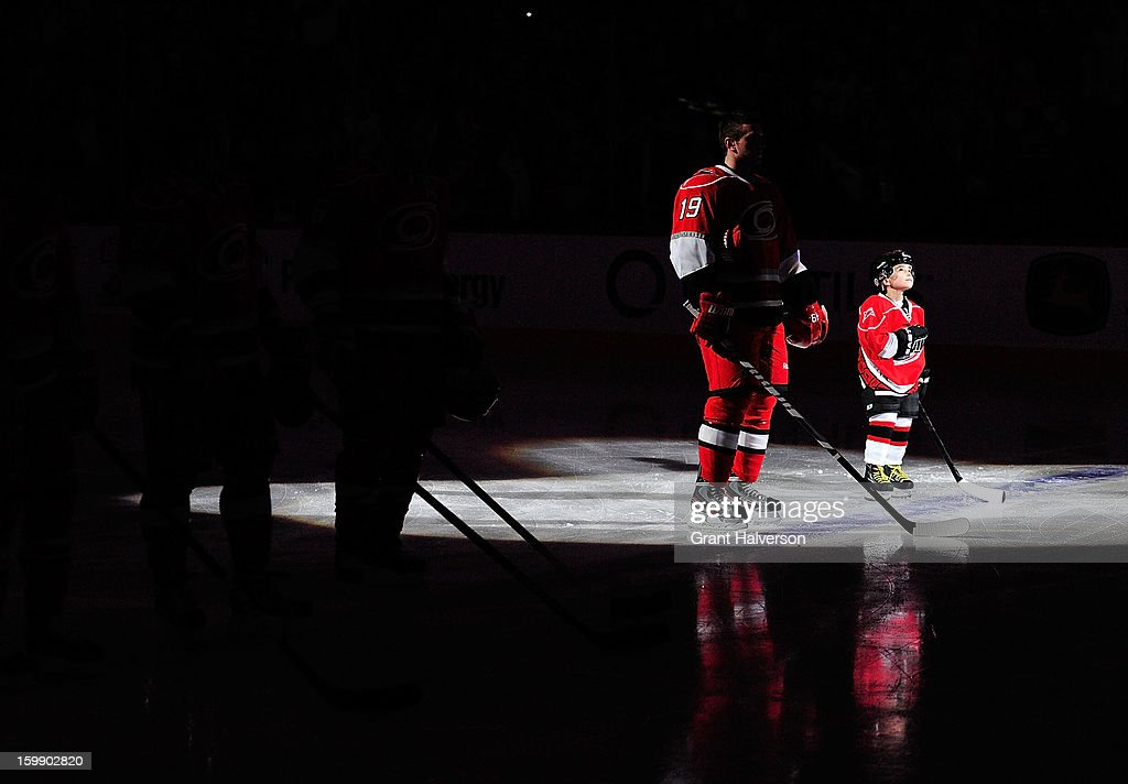 A young fan stands next to Jiri Tlusty #19 of the Carolina Hurricanes during the National Anthem before a game against the Tampa Bay Lightning at PNC Arena on January 22, 2013 in Raleigh, North Carolina.