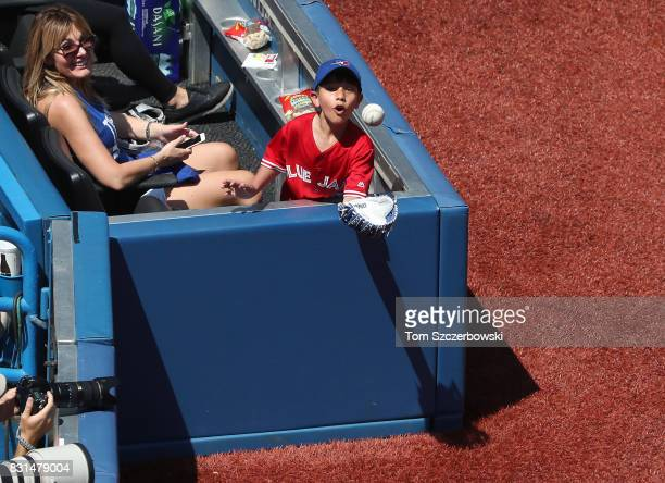 A young fan waits for a baseball that is thrown to him by Marcus Stroman of the Toronto Blue Jays after a foul ball was hit during MLB game action...