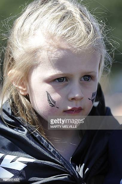 A young fan waits for New Zealand's All Blacks rugby team during a parade through the central business district of Wellington on November 6 following...