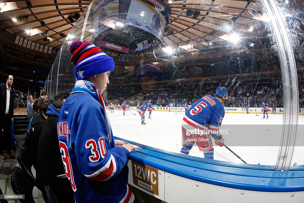 A young fan watches Dan Girardi #5 of the New York Rangers warm up before the game against the New Jersey Devils at Madison Square Garden on February 8, 2016 in New York City.