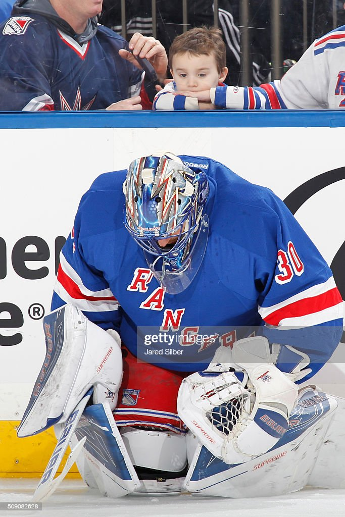 A young fan watches <a gi-track='captionPersonalityLinkClicked' href=/galleries/search?phrase=Henrik+Lundqvist&family=editorial&specificpeople=217958 ng-click='$event.stopPropagation()'>Henrik Lundqvist</a> #30 of the New York Rangers warm up before the game against the New Jersey Devils at Madison Square Garden on February 8, 2016 in New York City.