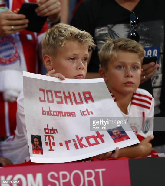 Young fans ask Joshua Kimmich of Bayern Munich for his shirt on their banner during the Bundesliga match between FC Bayern Muenchen and Bayer 04...