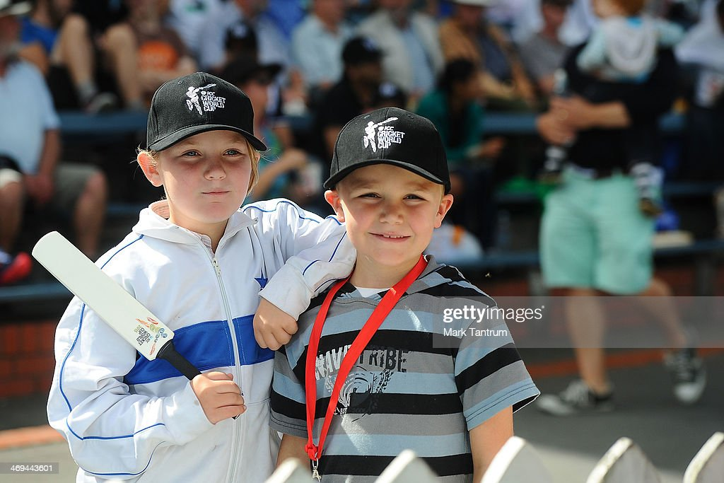 Young fans holding a cricket bat and wearing caps handed out during the 'One Year To Go' to the ICC Cricket World Cup announcement at The Basin Reserve on February 15, 2014 in Wellington, New Zealand.