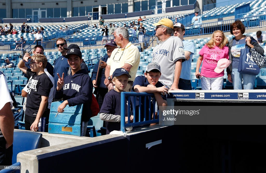 Young fans of the New York Yankees wait on the dugout for autographs just before the start of the Grapefruit League Spring Training Game against the Miami Marlins at George M. Steinbrenner Field on March 15, 2013 in Tampa, Florida.
