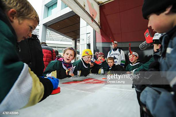 Young fans of the Vancouver Canucks play table hockey at the Spectator Plaza prior to the 2014 Tim Hortons Heritage Classic at BC Place on March 2...