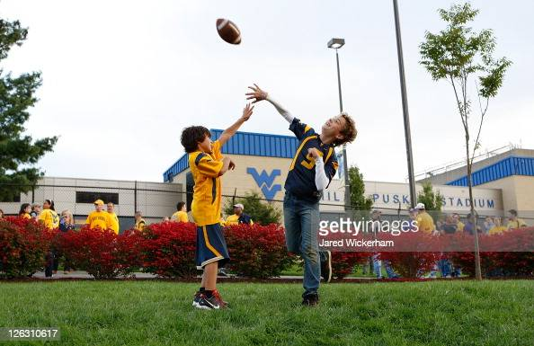 Young fans play football outside of Mountaineer Field prior to the game between the West Virginia Mountaineers and the Louisiana State University...