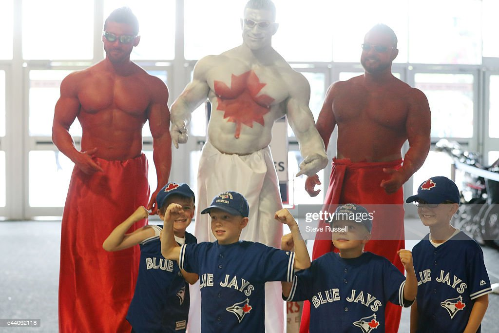 TORONTO, ON- JULY 1 - Young fans pose with some painted men as the Toronto Blue Jays play the Cleveland Indians on Canada Day at the Rogers Centre in Toronto. July 1, 2016.
