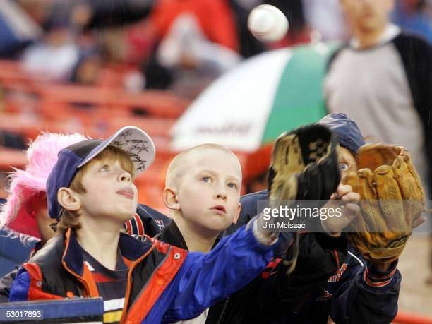 Young fans try to catch a ball thrown to them by a member of the San Francisco Giants during a rain delay before the start of the game between the...