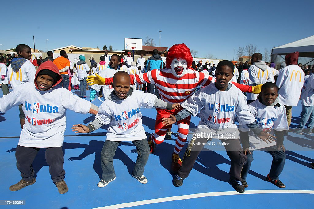Young fans with Ronald McDonald at the Pimville Boys and Girls Club basketball court dedication and clinic during the Basketball Without Boarders program in Johannesburg, South Africa.