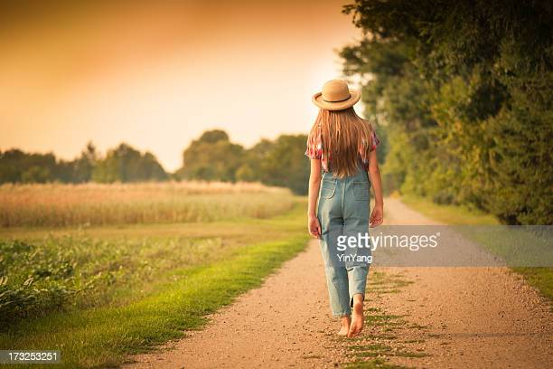 Young Farm Girl Walking in Country Road by the Field