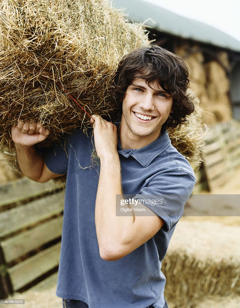 Young Farmer Carrying a Bale of Hay : Stock Photo