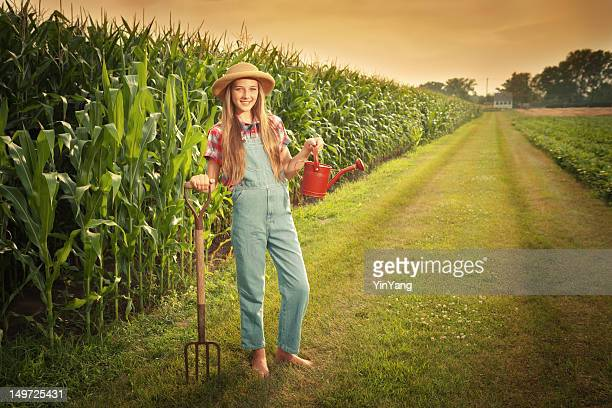 Young Farmer Girl Holding Gardening Tools by the Field Hz