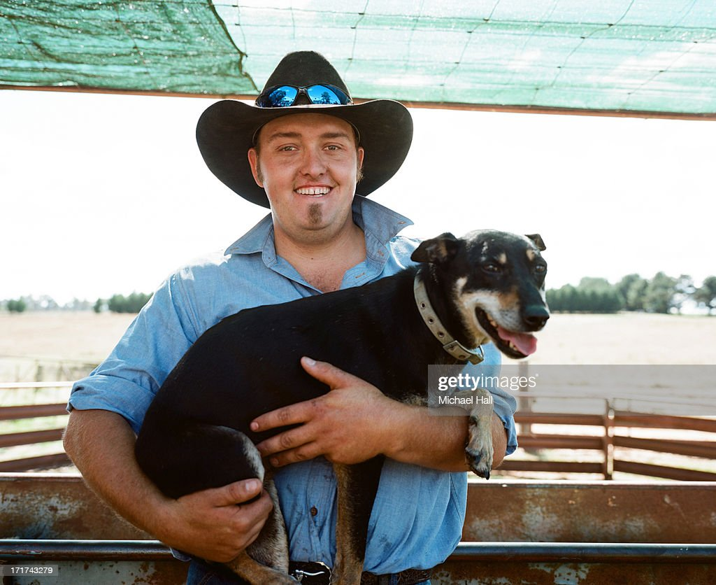 Young farmer holding farm dog : Stock Photo