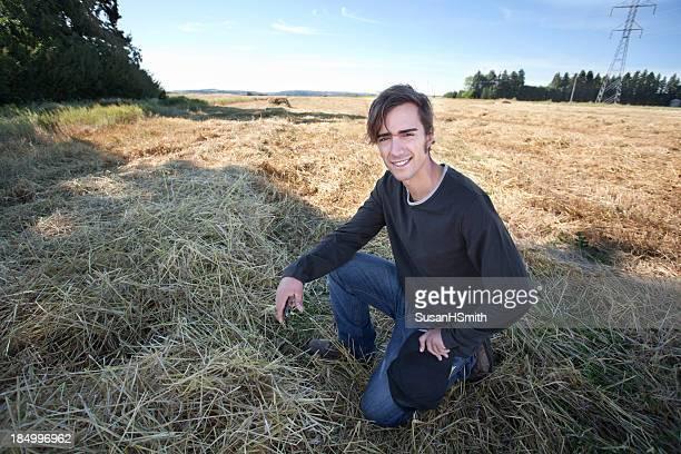 Jeune agriculteur dans le champ tenant le téléphone