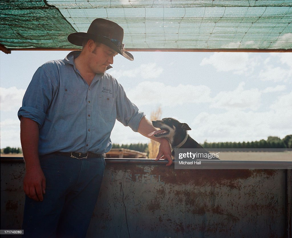 Young farmer looking at farm dog : Stock Photo