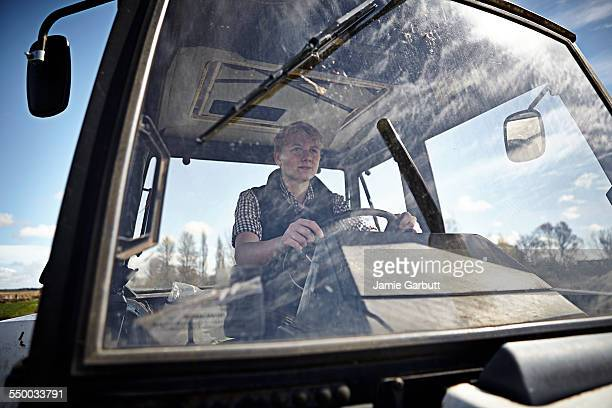 Young farmer sat driving a tractor on a sunny day