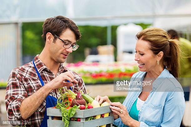 Young farmer talks about produce with customer