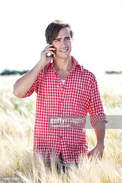 Jeune agriculteur avec le téléphone intelligent